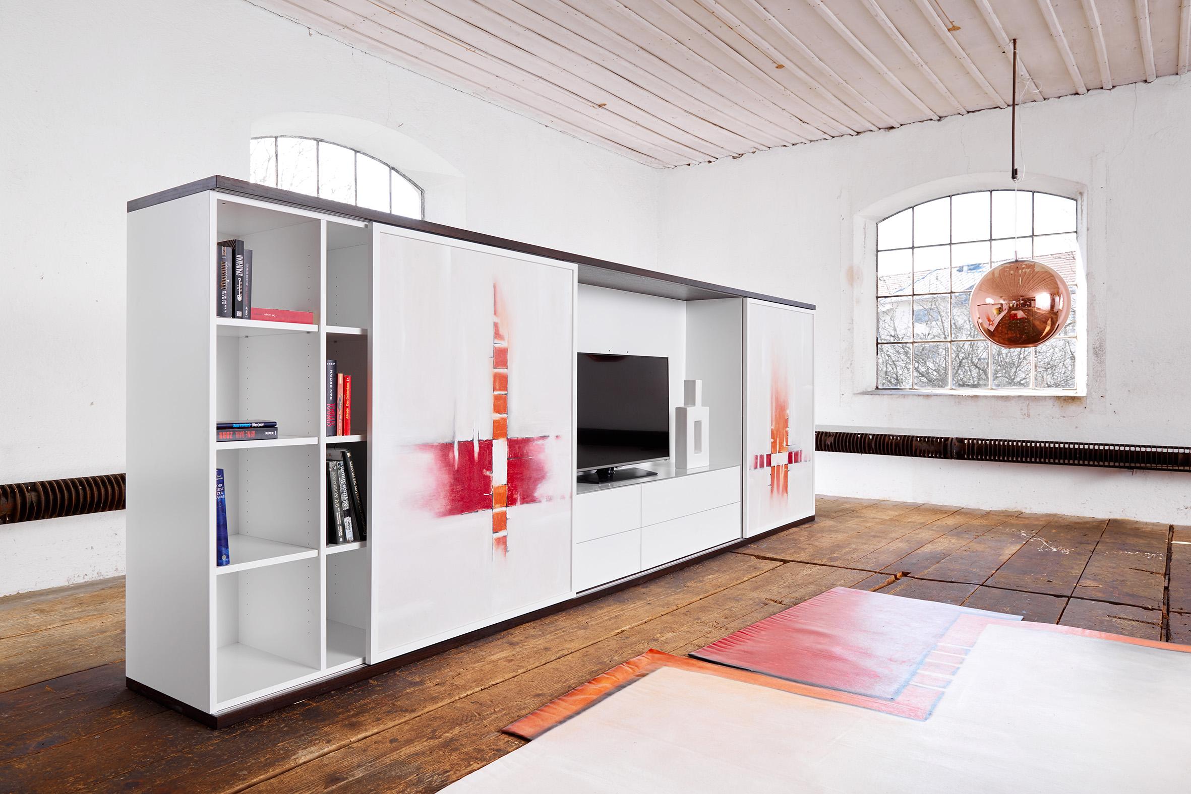 Die Gestaltung Des Möbels Nimmt Sich Durch Den Weißen Lack Deutlich Zurück  Und Lässt Die Farben Auf Dem Leinentuch Wirken. Der Passende Teppich Und  Die ...